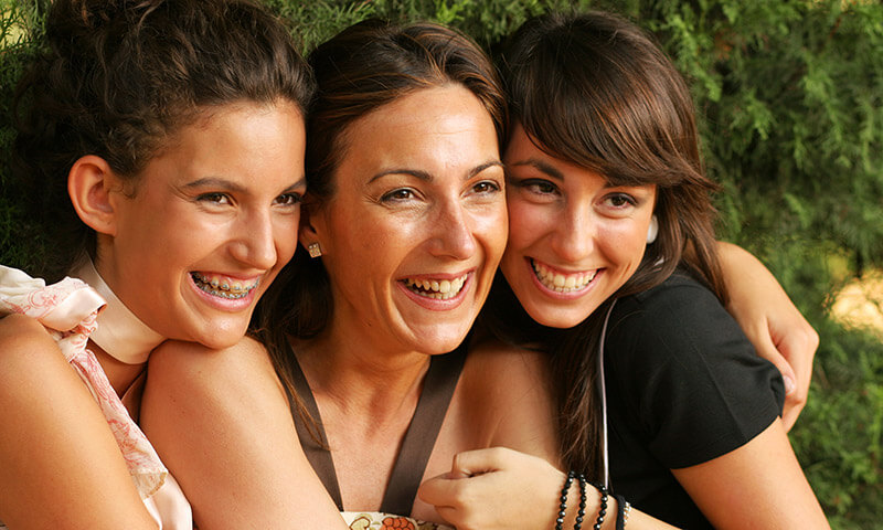 One smiling young lady with braces and two friends smiling beside her